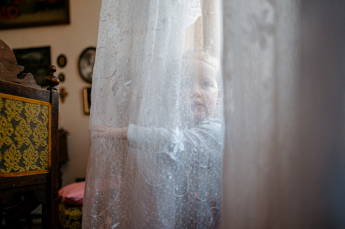 a girl is playing with a window curtain, opens is and smiles